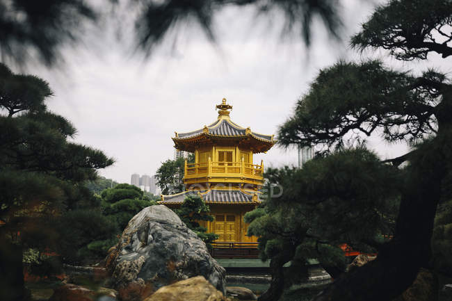 Vue extérieure du temple d'or entouré d'arbres, gratte-ciel au loin, Hong Kong, Chine — Photo de stock