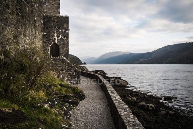 Château en mur surplombant un loch avec des montagnes au loin, Western Highlands, Écosse, Royaume-Uni — Photo de stock