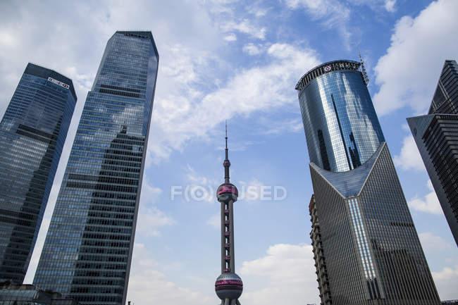Vista de bajo ángulo de los rascacielos que suben al cielo azul, Hong Kong, China - foto de stock
