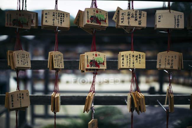 Close-up de tablets de madeira com mensagens escritas em japonês no santuário . — Fotografia de Stock