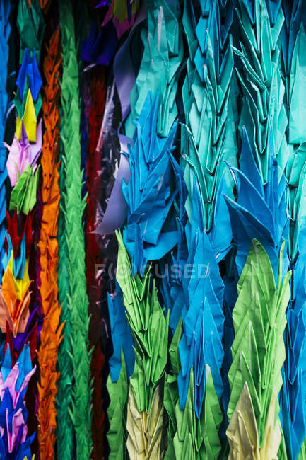 Close-up of colorful origami cranes, symbols of peace, decorating altar. — Stock Photo