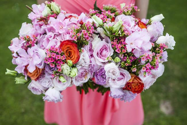 Großaufnahme einer Frau, die zwei Blumensträuße mit rosa Rosen in der Hand hält. — Stockfoto