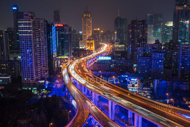 Elevated view of stacked road junction and Shanghai skyline at dusk, Shanghai, China — Stock Photo