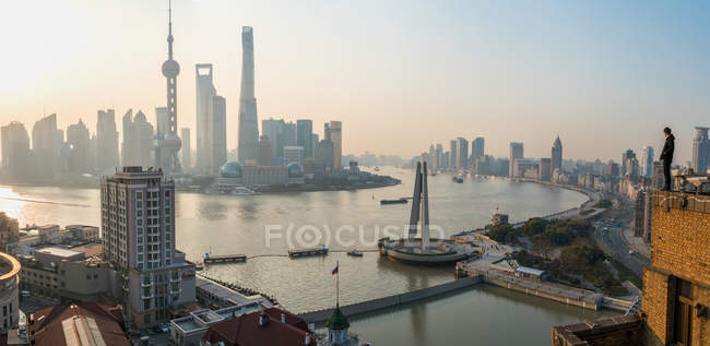 Silhouette of man admirating view over Huangpu River and Shanghai skyline in early morning, Shanghai, China. - foto de stock