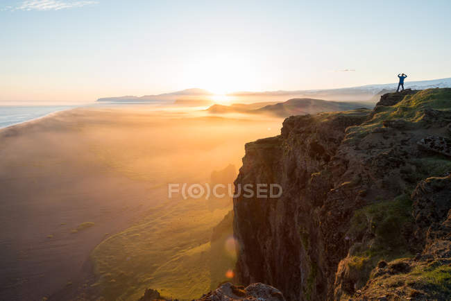 Silhouette of man looking at view at sunset from Dyrholaey Peninsula, Vik, South Iceland, Islandia. - foto de stock