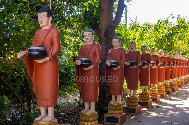 Reihe buddhistischer Mönchsstatuen mit roten Gewändern und Almosenschalen im Garten des buddhistischen Tempels in siem reap, Kambodscha — Stockfoto
