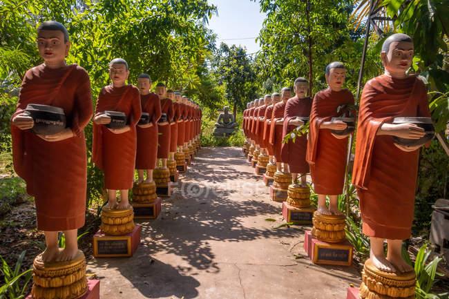 Reihen buddhistischer Mönchsstatuen mit roten Gewändern und Almosenschalen im Garten des buddhistischen Tempels in siem reap, Kambodscha — Stockfoto