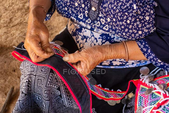 Mãos de mulher irreconhecível sentado costurando e fazendo vestuário tradicional, Vang Vieng, Laos — Fotografia de Stock