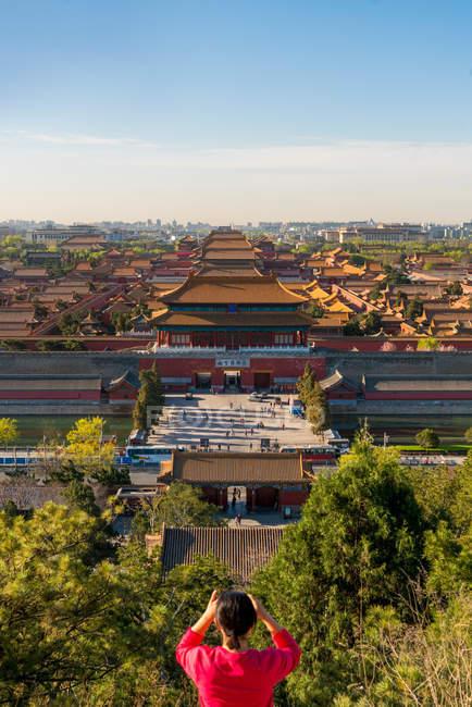 Vista general del turista femenino tomando fotos de la ciudad prohibida en Beijing, China. - foto de stock