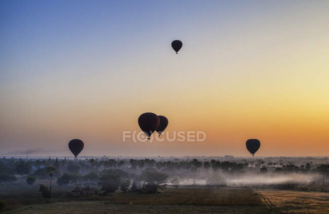 Hot air balloons over landscape with distant temples at sunset, Bagan, Myanmar. — Stock Photo