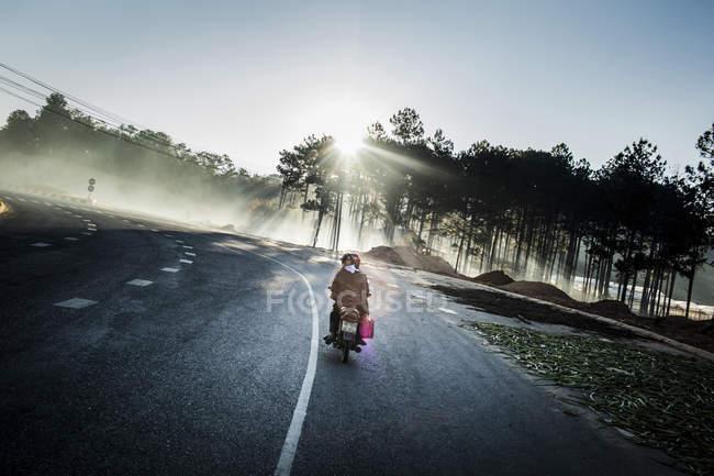 Visão traseira da moto dirigindo ao longo de uma estrada através da floresta com raios brilhantes no backlit . — Fotografia de Stock