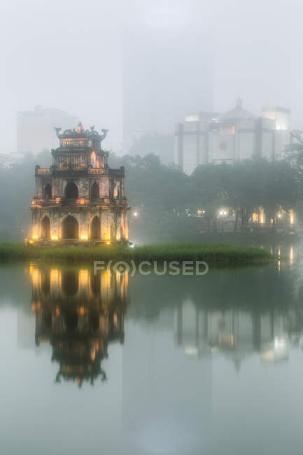 Exterior of illuminated temple reflected in lake at dusk, skyscrapers in distance, Hanoi, Vietnam. — Stock Photo