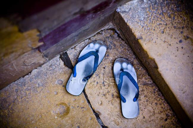 Alto ângulo close-up de par de sandálias azuis desgastadas fora nas portas . — Fotografia de Stock