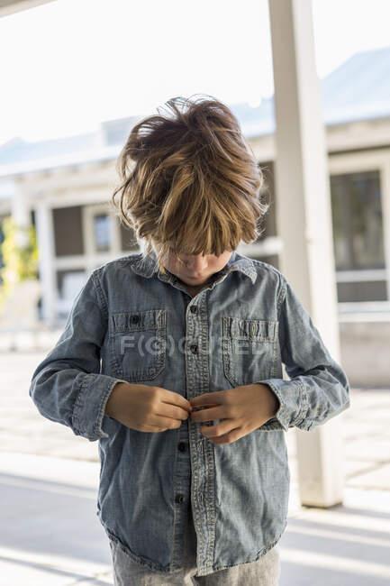 6-летний мальчик застегивает джинсовую рубашку — стоковое фото