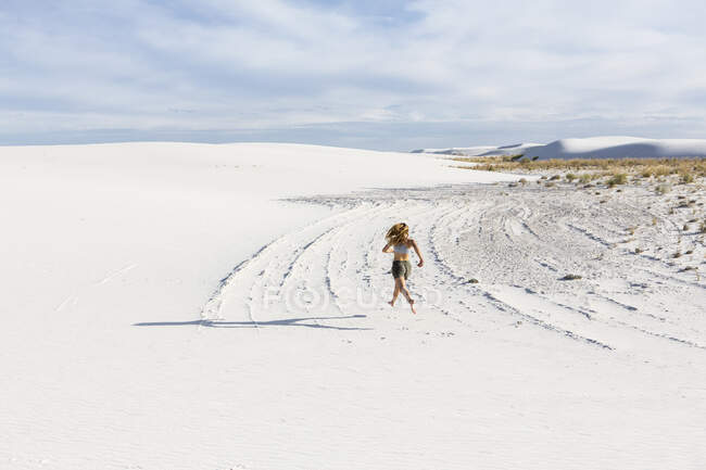 Teenage girl running in the sand, White Sands Nat'l Monument, NM — Stock Photo