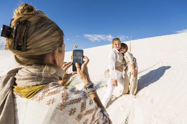 Uma mulher tirando foto de seus filhos com um telefone inteligente na paisagem de dunas de areia branca sob céu azul. — Fotografia de Stock