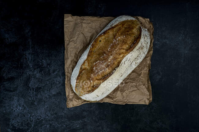 Высокий угол вблизи свежеиспеченной буханки хлеба на черном фоне. — стоковое фото