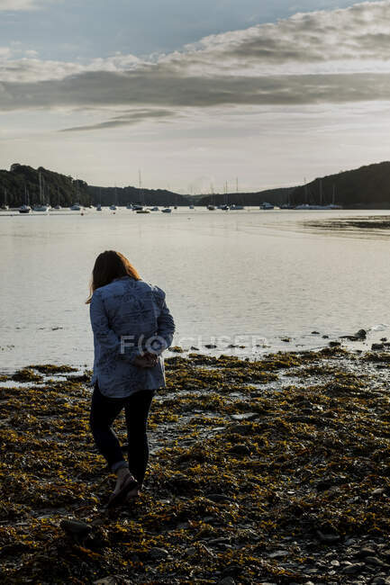Rear view of woman standing on a beach at sunset, with sailboats and cliffs in the distance. — Stock Photo