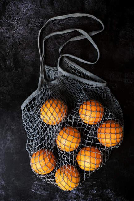 Alto angolo primo piano di arance in borsa a rete grigia su sfondo nero . — Foto stock