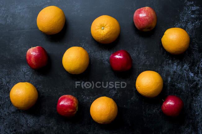 Високий кут, близький до червоного яблука та апельсинів на чорному тлі.. — стокове фото