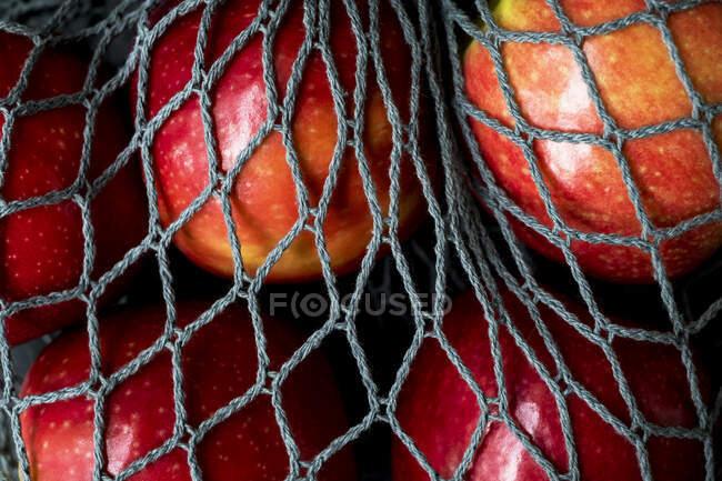 Haut angle gros plan de pommes rouges dans un sac filet gris sur fond noir . — Photo de stock