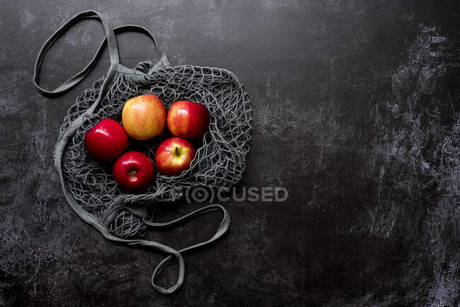 High angle close up of red apples in grey net bag on black background. — Stock Photo