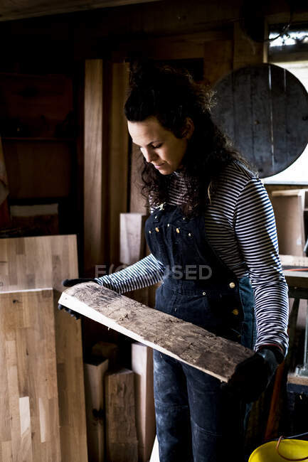Woman with long brown hair wearing dungarees standing in wood workshop, holding piece of wood. — Stock Photo