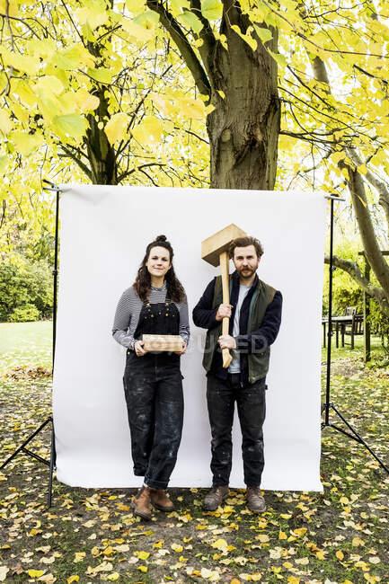 Retrato de la mujer y el hombre portador sosteniendo bloques de madera de pie frente al fondo blanco en un jardín, mirando la cámara.. - foto de stock