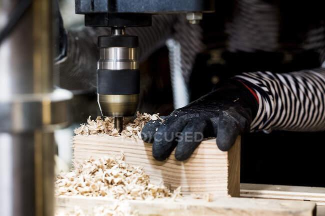 Закрытие человека в защитных перчатках с помощью электрического дрилла в мастерской по дереву. — стоковое фото