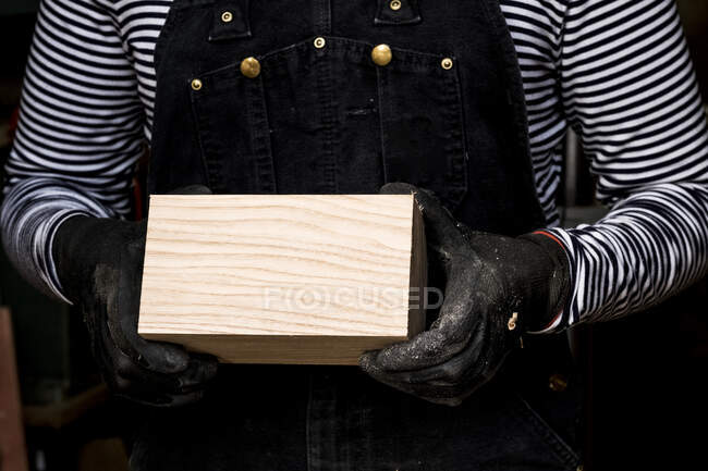 Nahaufnahme einer Person mit Schutzhandschuhen, die einen Holzblock hält. — Stockfoto