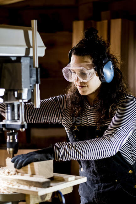 Woman with long brown hair wearing dungarees, safety glasses and ear protectors standing in wood workshop, using electric drill. — Stock Photo