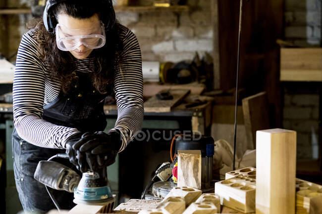Женщина с длинными каштановыми волосами в балахонах, защитных очках и ушных протекторах, стоящая в деревообрабатывающей мастерской, с использованием сандера. — стоковое фото