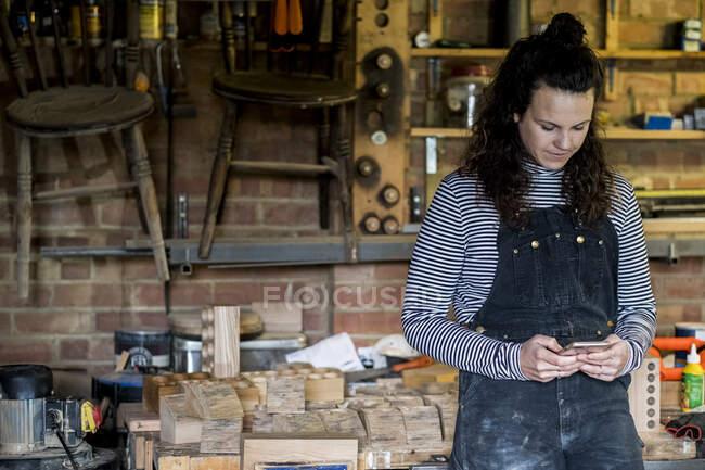 Женщина с длинными каштановыми волосами в балаклавах стоит в мастерской по дереву, пользуясь мобильным телефоном. — стоковое фото