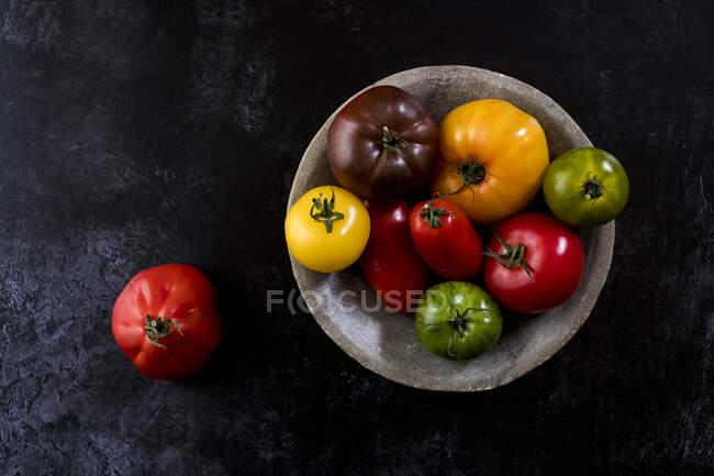 Высокий угол крупного плана серой тарелки с выбором помидоров разных цветов и оттенков на черном фоне. — стоковое фото