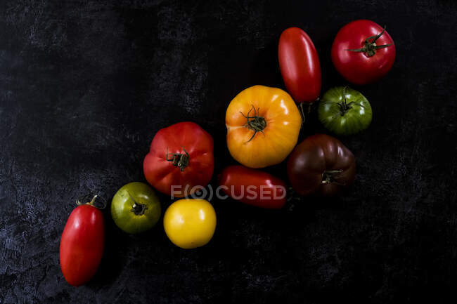 High angle close up of a selection of tomatoes in various shapes and colours on black background. — Stock Photo
