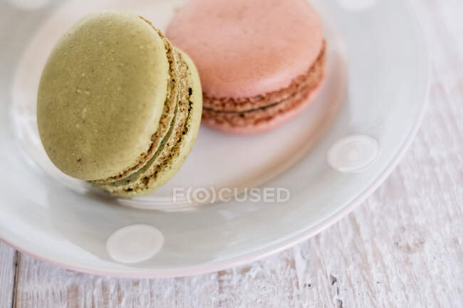 High angle close up of two macaroons on a white plate. — Stock Photo