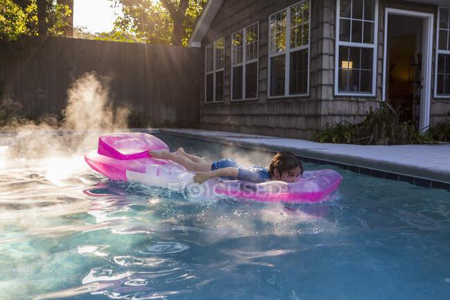 Un garçon de 6 ans joue dans la piscine au lever du soleil — Photo de stock