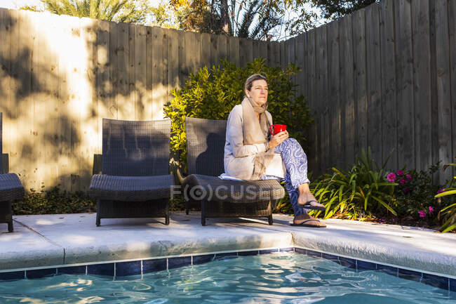 Жінка сидить на сонечку біля басейну. — стокове фото