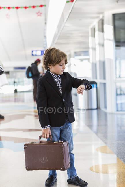 Un garçon de 6 ans regarde sa montre à l'aéroport — Photo de stock