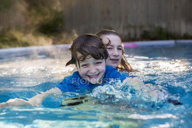 Frères et sœurs jouant dans la piscine tôt le matin — Photo de stock