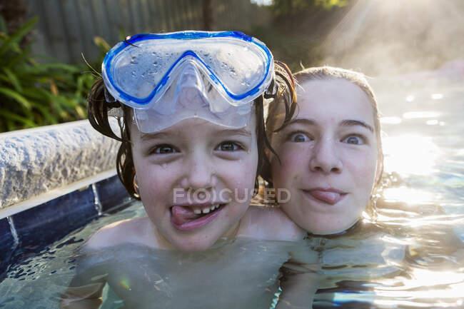Une adolescente et son frère dans une piscine chaude, regardant la caméra, sortant leur langue. — Photo de stock