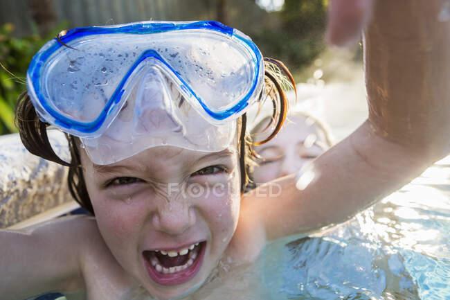 Garçon en lunettes de protection riant devant la caméra, dans une piscine chaude avec sa sœur. — Photo de stock