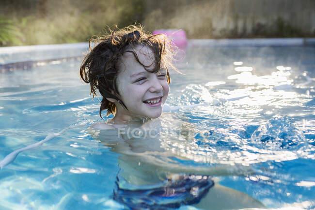 Garçon de six ans nageant dans une piscine chaude. — Photo de stock