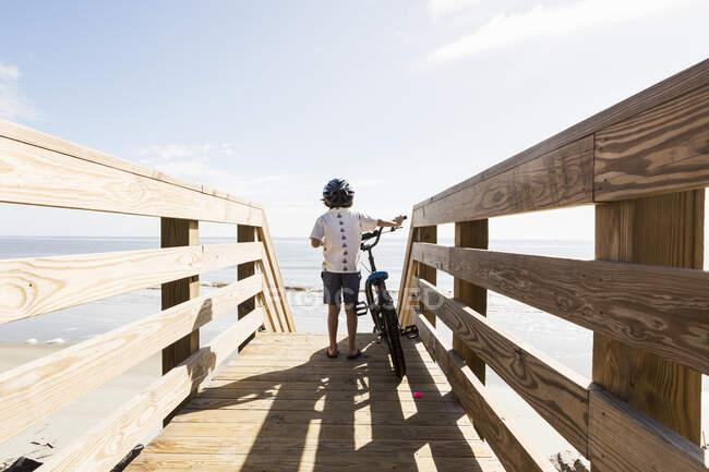 6-летний мальчик на деревянном мостике со своим велосипедом — стоковое фото