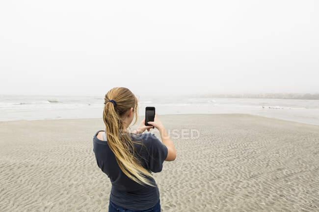 Adolescente falando fotos com telefone inteligente na praia, St. Simon 's Island, Georgia — Fotografia de Stock