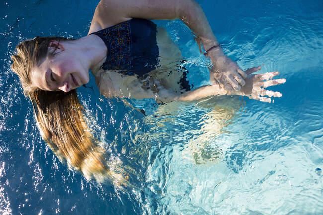 Une adolescente dans une piscine, ses longs cheveux blonds s'envolent dans l'eau. — Photo de stock