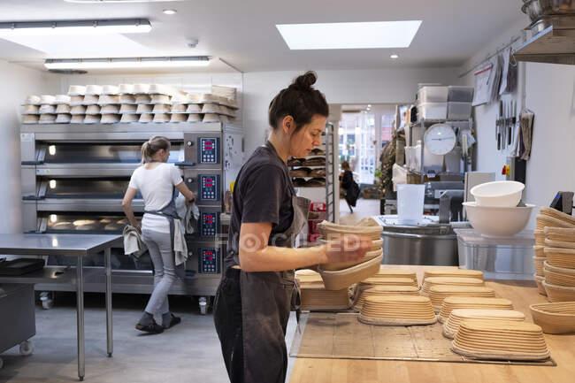 Женщина в фартуке, стоящая в ремесленной пекарне, готовящая корзины . — стоковое фото