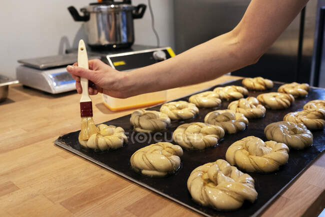 Close up person brushing cinnamon buns on a baking tray in an artisan bakery. — Stock Photo