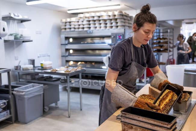 Женщина в перчатках и перчатках, стоящая в пекарне, выпекает свежеиспеченные хлебы . — стоковое фото