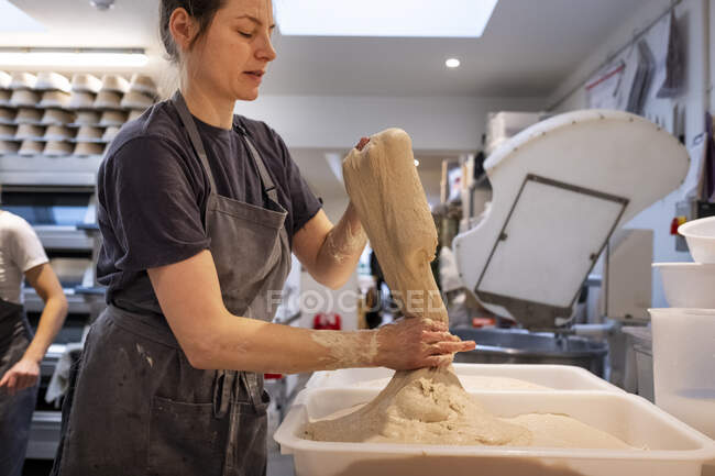 Woman wearing apron standing in an artisan bakery, working with sourdough. — Stock Photo